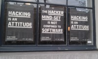 Amsterdam hacking signs in a canal-front window.