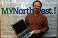 Charles Brennick of InterConnection with one of the group's $149 refurbished laptops for low-income households.