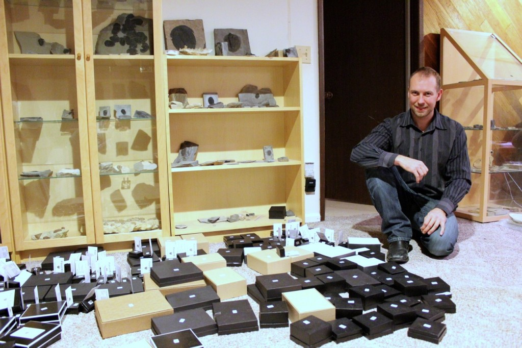 Startup vet and developer Matt Heaton inside his basement, which doubles as the temporary headquarters for FossilEra. The small boxes are fossils ready to be shipped out to customers.