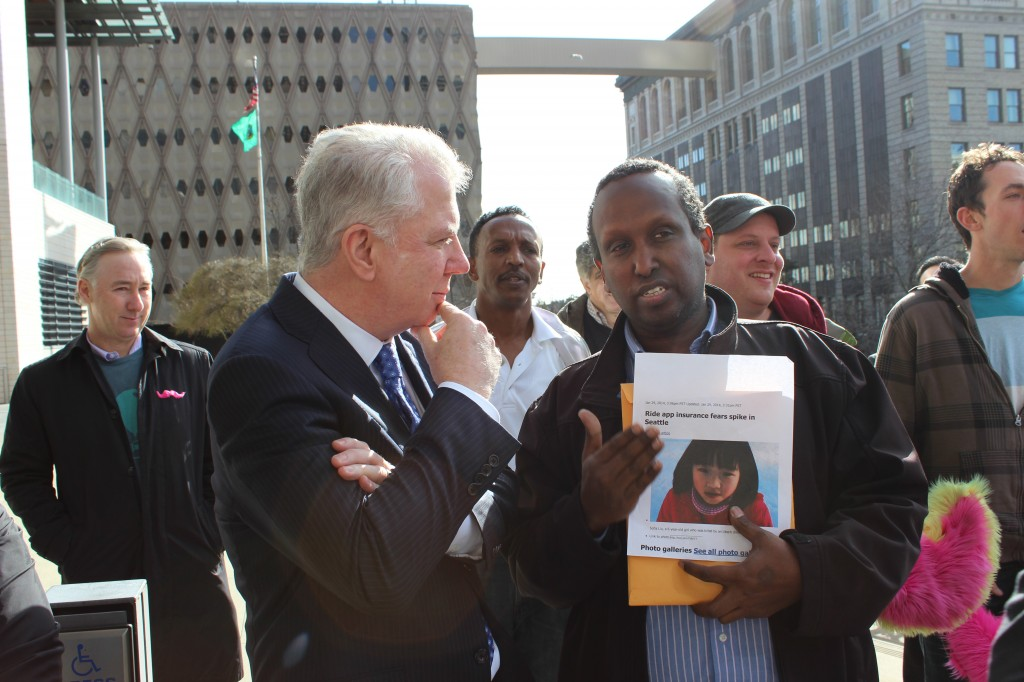 Eastside For-Hire manager Samatar Guled speaks to Mayor Ed Murray during a rally last month in support of ride-sharing startups.
