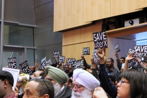 UberX supporters wave posters during a City Council meeting in March.