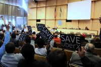 UberX supporters hold signs at a City Council meeting on March 17.