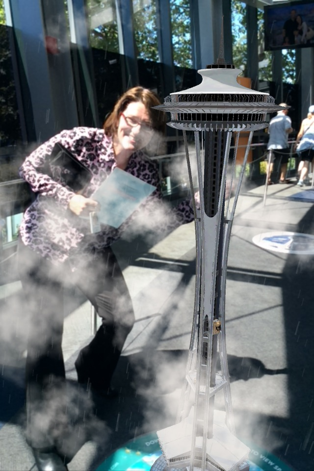 Karen Olson, vice president of marketing for the Space Needle, poses with the virtual Needle that rises from one of 18 new Space Spots. (Photo: Mónica Guzmán)