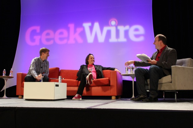 John Cook, left, and Todd Bishop, right, interview T-Mobile CEO John Legere at the 2014 GeekWire Summit