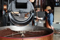 A Starbucks employee works with a fresh batch of just-roasted coffee beans at the company's new shop in Capitol Hill.