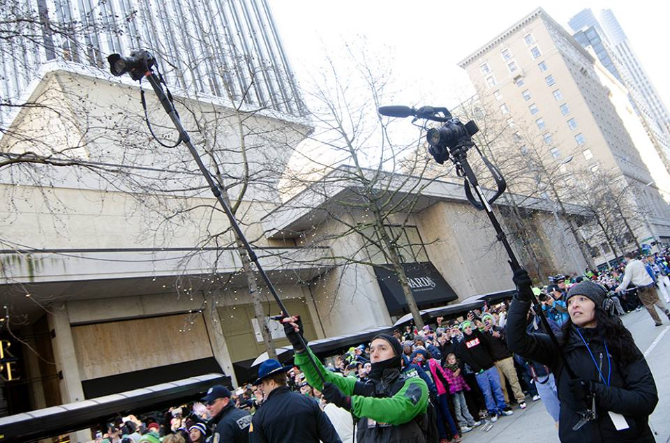 Seattlepi.com photographer Josh Trujillo and Seattle Times photographer Genevieve Alvarez use monopods to elevate their cameras above the crowds during the 2014 Seahawks victory parade. (Photo: Daniel Berman Photography)