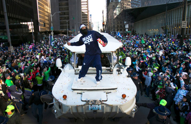 Marshawn Lynch scatters Skittles into the crowd during the Seahawks victory parade. (Photo: Josh Trujillo, Seattlepi.com. And his monopod)