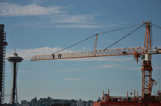 A construction crane hovers over Seattle, with the iconic Space Needle in the background. Photo via Flickr Creative Commons.