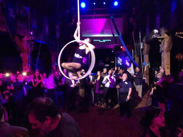 A performance artist swings above the crowd at the Qumulo launch party.