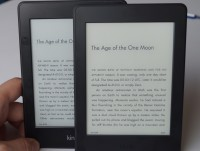 The new Paperwhite with the Kindle name in black in the bezel, in front of the original Paperwhite.