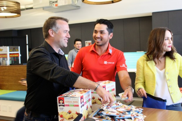Jason Day (center) packs backpacks with food with Concur Chief Marketing Office Jerame Thurik and President Elena Donio.