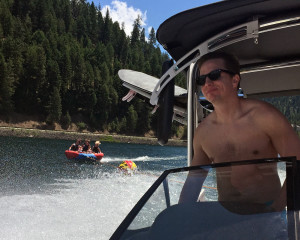 etailz CEO Josh Neblett driving boat with employees on innertube