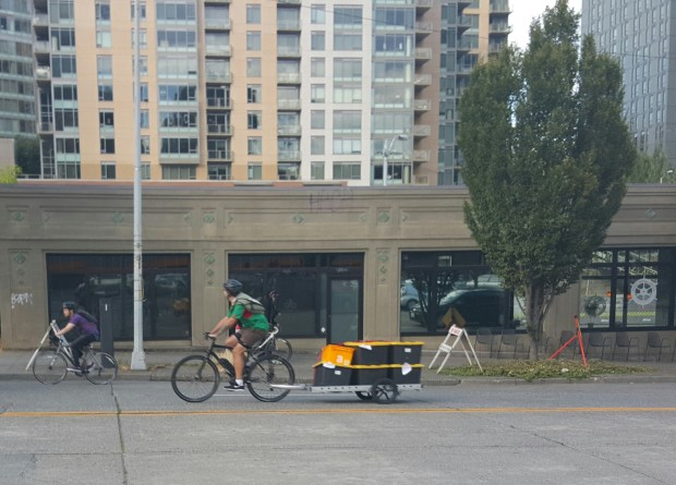 An AmazonFresh delivery rider carries groceries through Seattle.