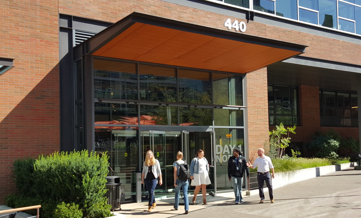 Workers come and go at Amazon's campus in Seattle. (GeekWire File Photo.)