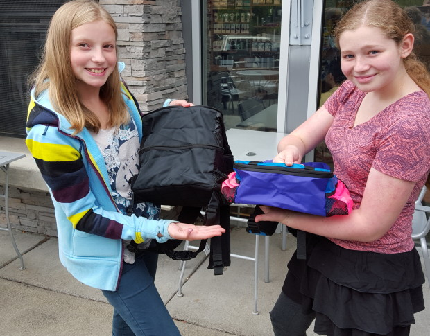 Entrepreneurs Logan Richards, left, and Suzy Mahlman show their SuziLlo backpacks when unzipped and expanded, and in its smaller size. Photo: Lisa Stiffler.