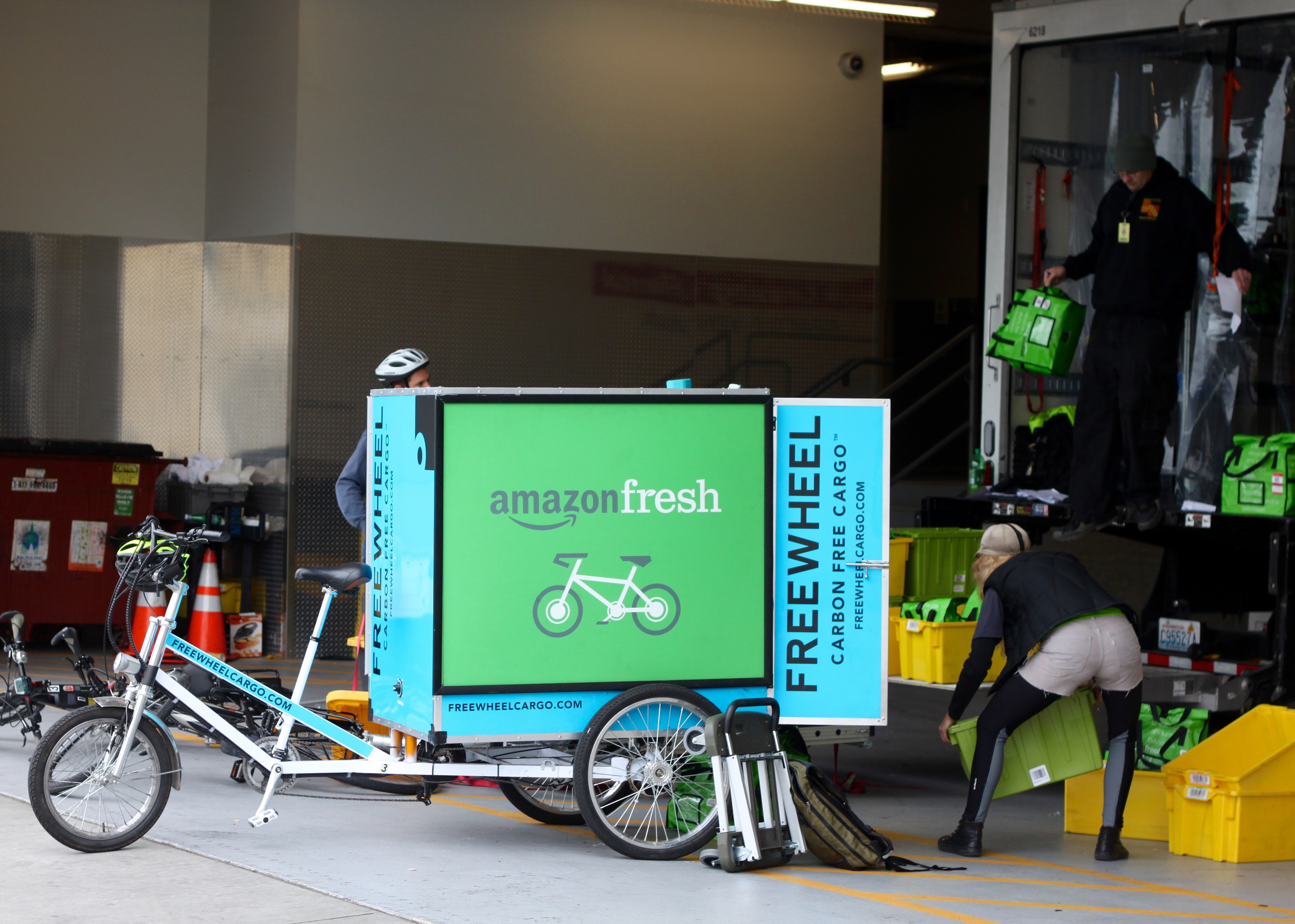 AmazonFresh workers load a cart for delivery in Seattle.