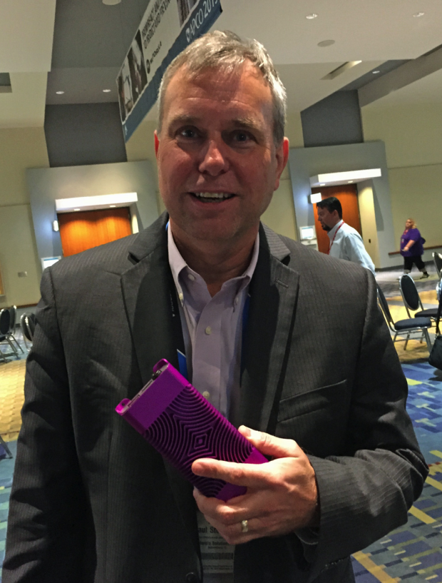 "Motorola Chief Technology Officer Paul Steinberg holds an LTE cell site ""in a box."" Photo from the Annual Conference of the Association of Public Safety Communications Officials (APCO) on August 16, 2015, by Bill Schrier."