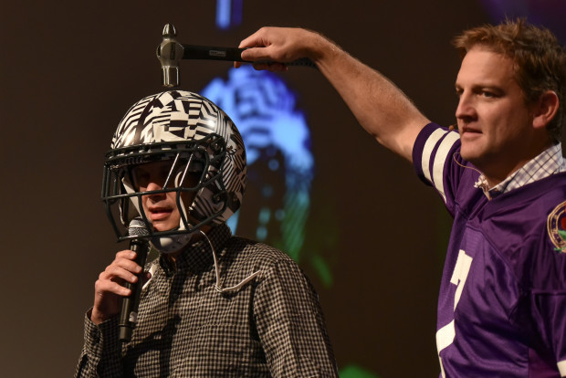 Former NFL and University of Washington quarterback Damon Huard tests out Vicis' helmet worn by GeekWire co-founder John Cook at the GeekWire Summit last year.
