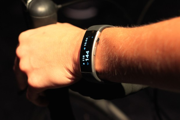 A Microsoft worker demonstrates the new Microsoft Band on a stationary bicycle.