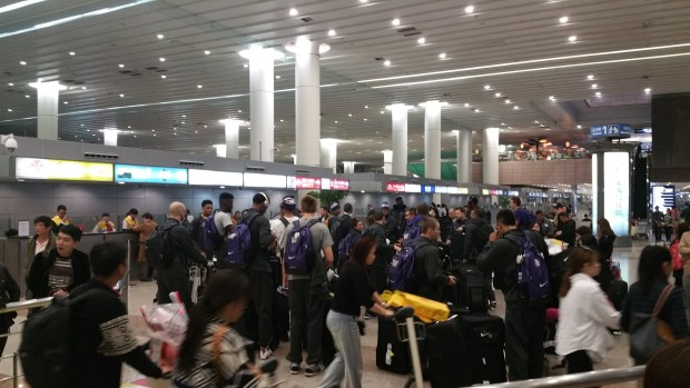 The UW players arrive at the Shanghai airport, with many interested Chinese looking on.