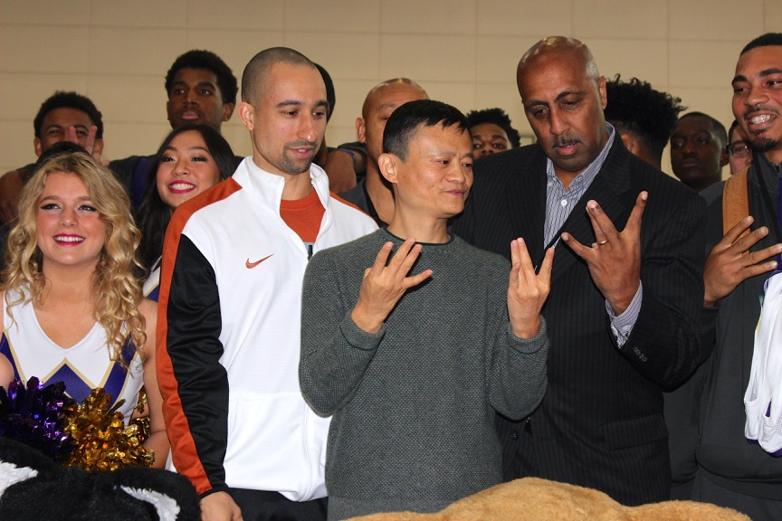 "UW men's basketball coach Lorenzo Romar teaches Alibaba founder Jack Ma how to properly do the ""W"" symbol on Tuesday at Alibaba's campus. Texas head coach Shaka Smart is on the left."