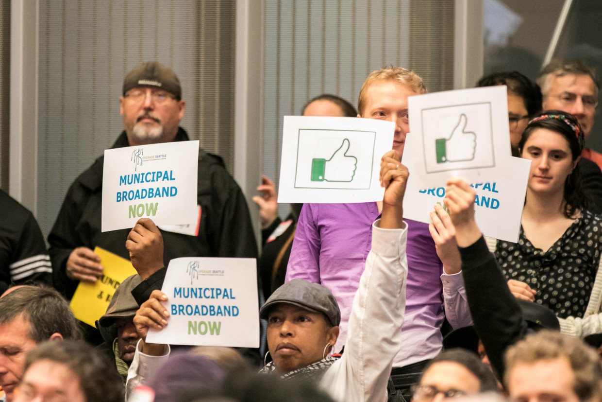 Municipal broadband supporters holding signs at today's Seattle City Council vote. (Photo from the office of council member Kshama Sawant)