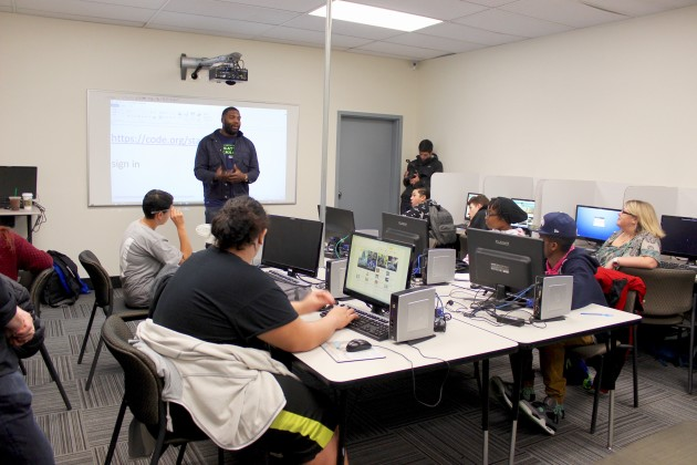Russell Okung addresses the students before class on Tuesday.