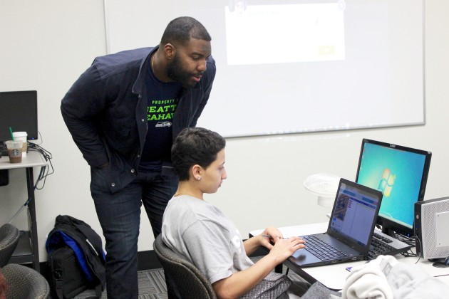 Seahawks lineman and GREATER co-founder Russell Okung watches as Peyton Rentz learns the basic of computer science at the Seattle Urban Academy earlier this week.