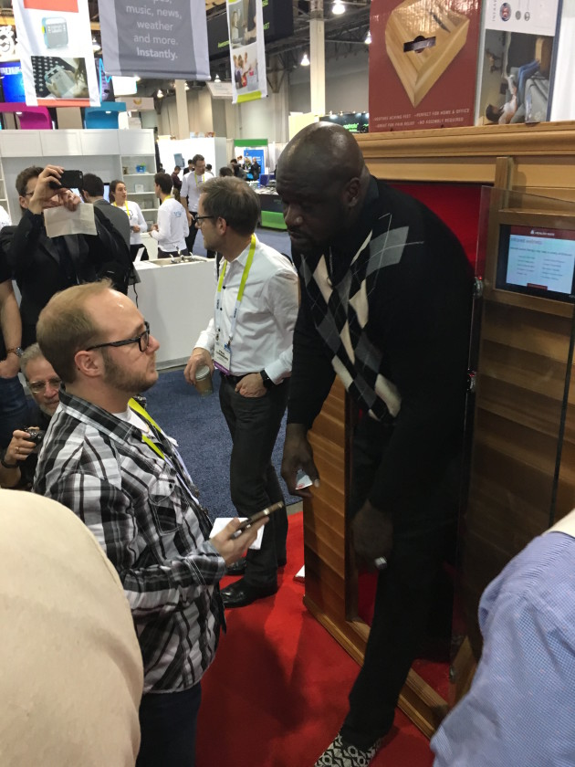 Shaq emerges from a foot warming hut at the Lifesmart booth
