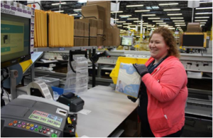 An Amazon employee prepares to ship the Kent facilities first package.