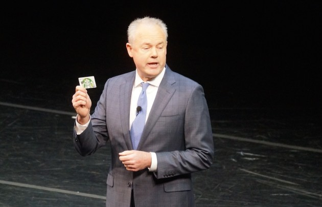 Starbucks Presdient Kevin Johnson shows the new Starbucks prepaid card at the company's shareholders meeting last month.