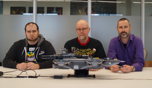 Senior producer Justin Woods, studio operations director William Schmitt and art director Leigh Kellogg sit behind a Lego Helicarrier in the studio's main conference room.