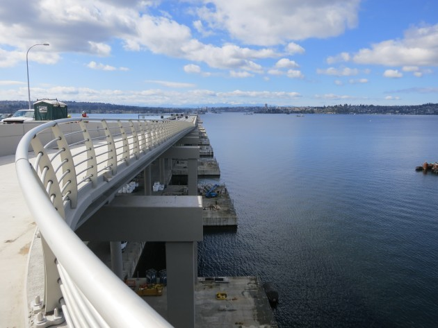 With the bike path railing stretching toward Seattle above, pontoons are visible below on the north side of the bridge. (Kurt Schlosser / GeekWire)