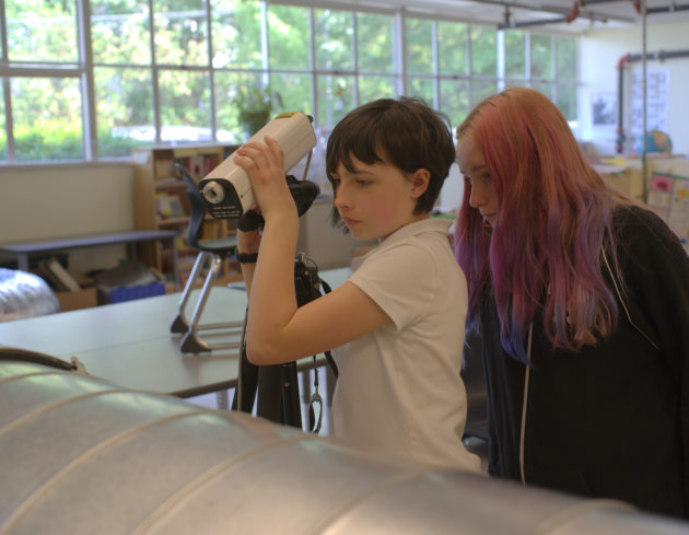 Carmen Olsen lines up a laser pointed into a wind tunnel as her science fair partner, Erin Hunt, looks on. Both girls are in sixth grade and attend Louisa Boren STEM K-8. (Lisa Stiffler / GeekWire)