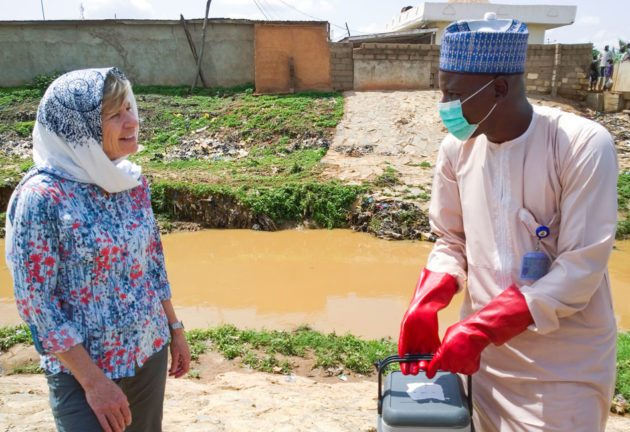 Environmental health officer Haliru Usman testing sewage for the polio virus in Nigeria with Sue Desmond-Hellmann. (Photo via Gates Foundation)