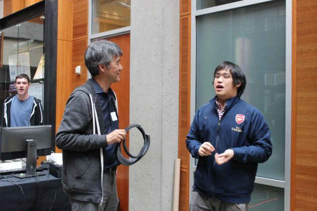 Microsoft Research Corporate Vice President Peter Lee (left) speaks with UW student Panji Wisesa.