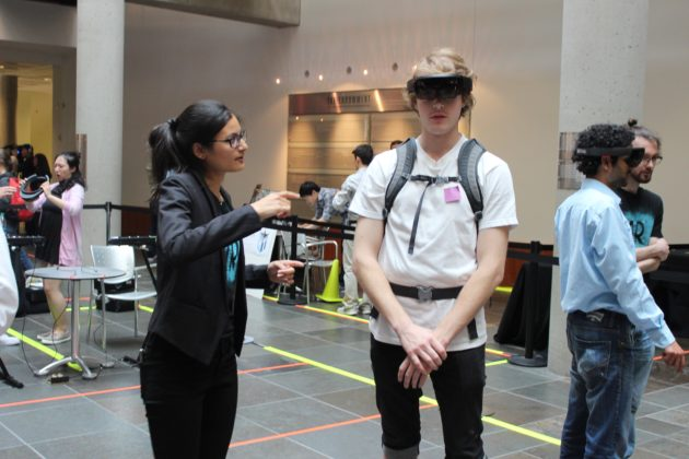 UW fifth-year grad students Sonja Kahn helps guide a user through her team's HoloLens app.