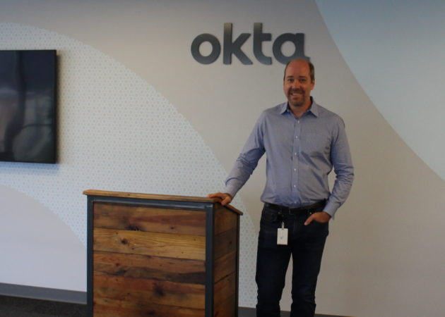 "Allen Clark, Okta's VP of partnerships, poses in the ""all-hands"" area, where full-staff meetings are held. (GeekWire Photo / Dan Richman.)"