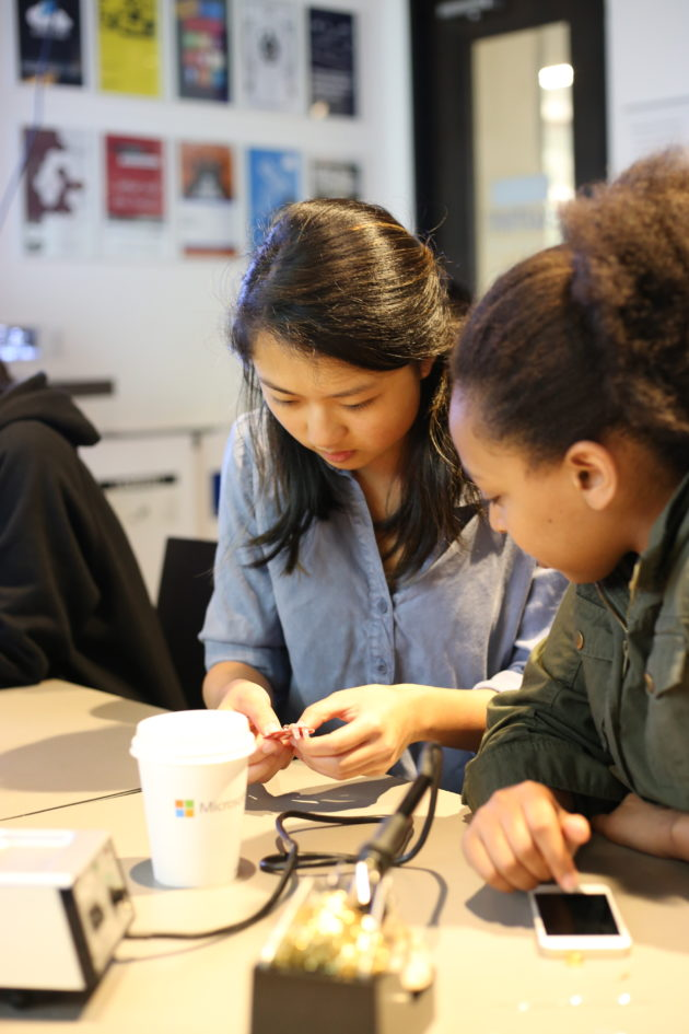 Lily Wang, a Microsoft employee and one of the Summer Immersion Program mentors, assists Solome Taye, who is starting her senior year at Foster High School in Tukwila, located south of Seattle. Taye said she's interested in going into technology not only despite the fact that men outnumber women, but because of the disparity. (Microsoft Photo)