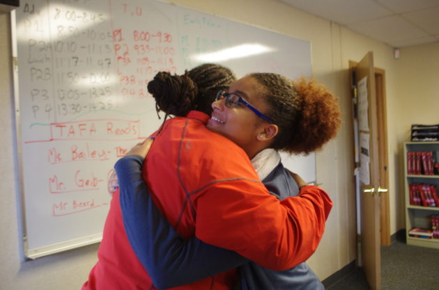 TAF Academy is more hugs than handshakes as TAF co-founder and executive director Trish Millines Dziko greets student Artina Daniels during calculus class. (Lisa Stiffler / GeekWire)