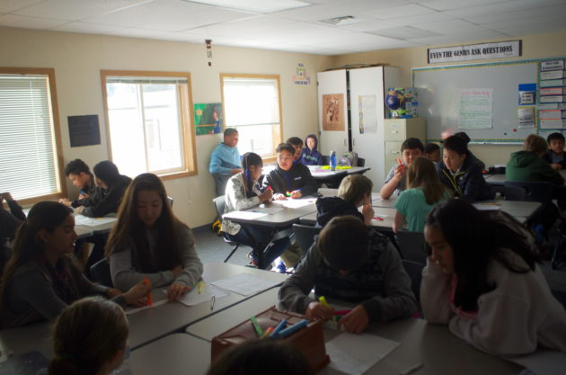 Eighth-grade students give each other feedback on assignments and assess their own performance. (Lisa Stiffler / GeekWire)