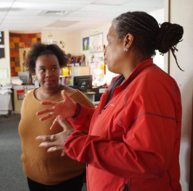 Dziko, right, talks teaching with eighth-grade humanities instructor Ashleigh Shoecraft. (Lisa Stiffler / GeekWire)