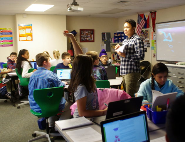 Seventh-grade humanities teacher Carlito Umali explains a homework assignment to his students at TAF Academy. (Lisa Stiffler / GeekWire)