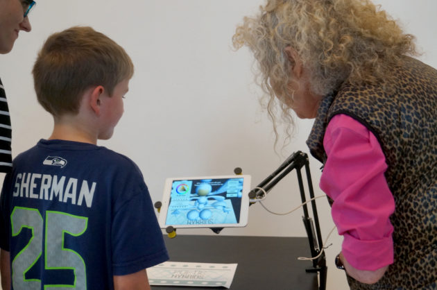 Artist Ginny Ruffner (right) shows her work to a young visitor at the exhibit.