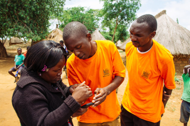 Ephraim Sikalundu, left, Data collector, and Vincent Munsaka, right, Community health worker stand with Racheal Mokosha, District Malaria Focal Person, looking at a mobile phone, with the grass-roofed huts of Harmony village behind them