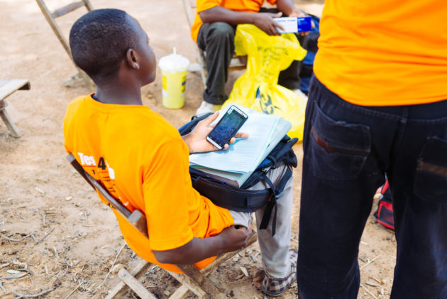 In Sinafala village, a man, Odinga Chitonka, data collector, sits hodling a mobile phone, papers, and a backpack.