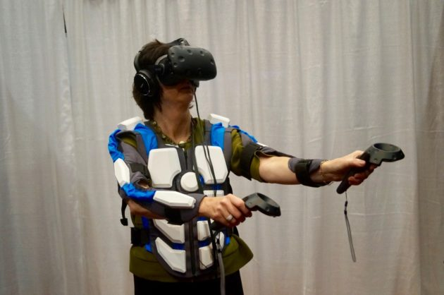Bellevue City Councilmember Lynne Robertson tries out NullSpace's virtual reality suit and HTC Vive. Nat Levy / GeekWire Photo.
