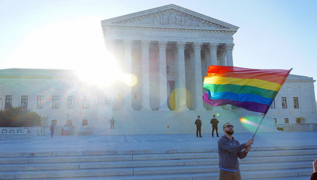A demonstrator waves the LGBTQ flag outside the Supreme Court. (Flickr Photo via Ted Eytan).