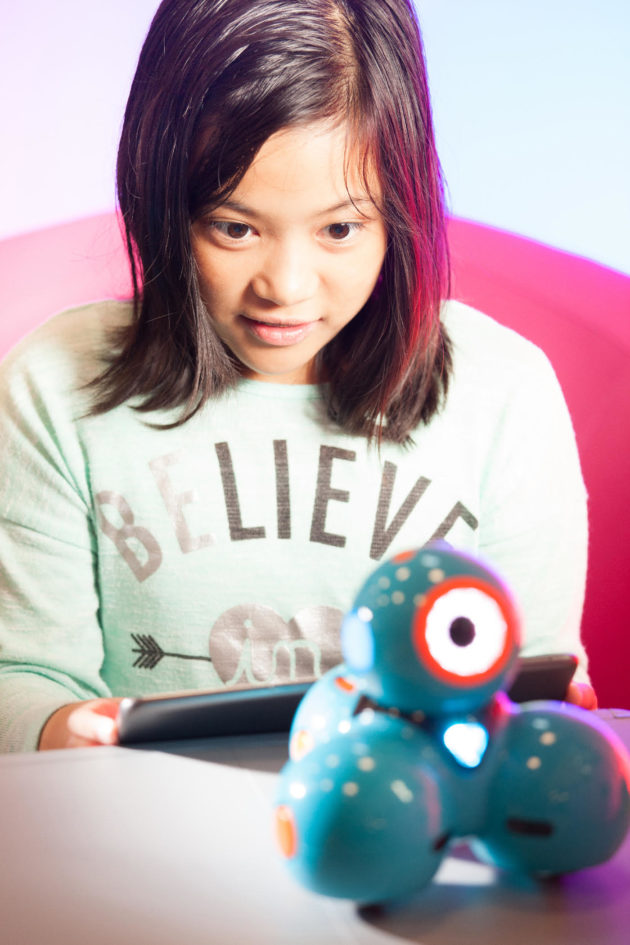 (Dash Robot) A young girl plays with Dash, a programmable robot by Wonder Workshop. Courtesy of LCM+L.