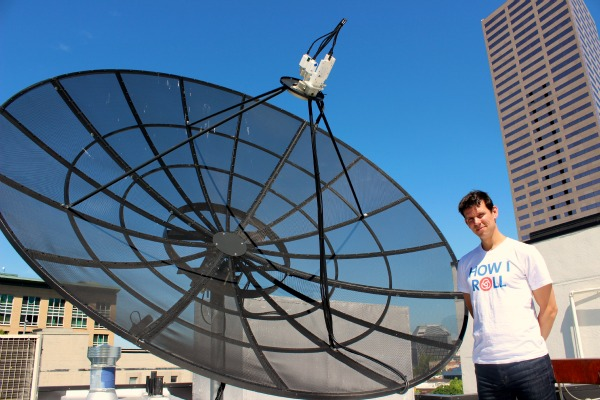 Elemental CEO Sam Blackman stands on top of the company HQ in downtown Portland with one of its big satellites.
